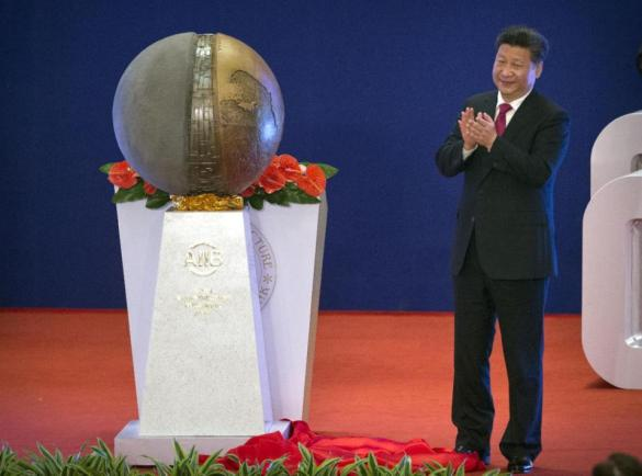 Chinese President Xi Jinping applauds after unveiling a sculpture during the opening ceremony of the Asian Infrastructure Investment Bank (AIIB) in Beijing Saturday, Jan. 16, 2016. (AP Photo/Mark Schiefelbein, Pool)